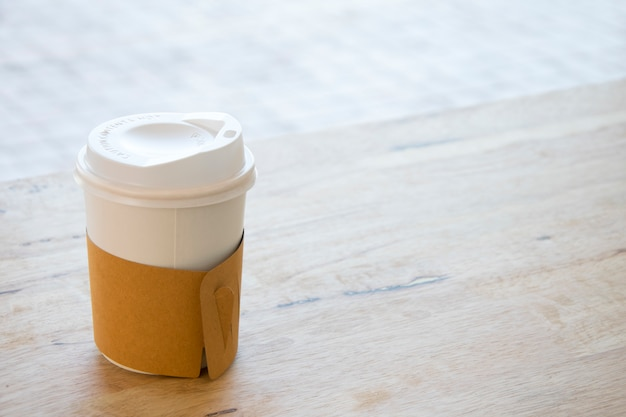 Hot coffee in paper cup isolated on wood table background