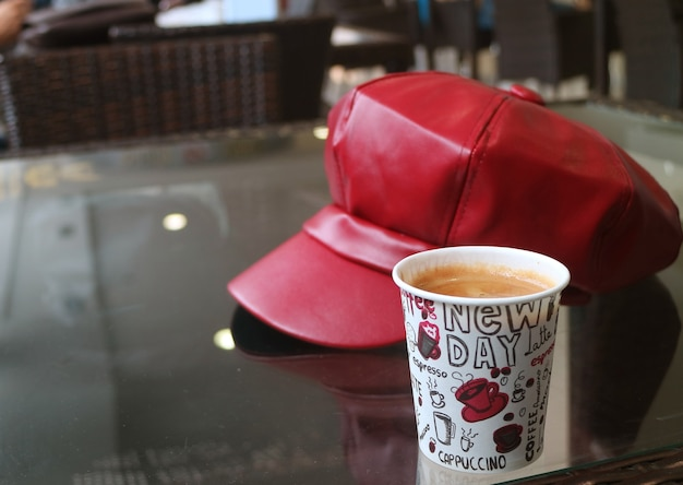 Hot coffee in paper cup with blurry red cap on the table