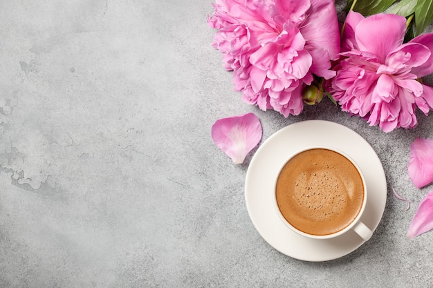 Hot coffee and pink peony flowers