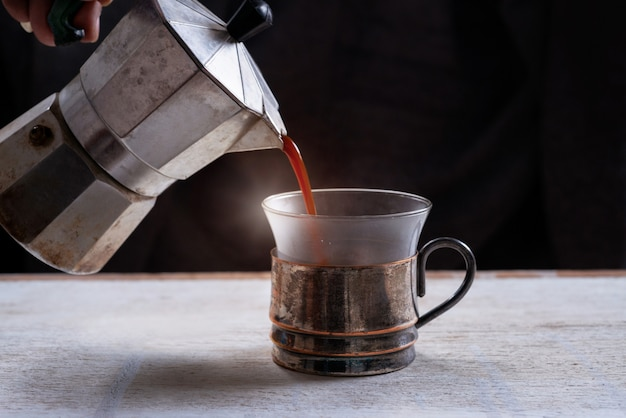 Hot coffee pouring from coffee pot into cup, black background
