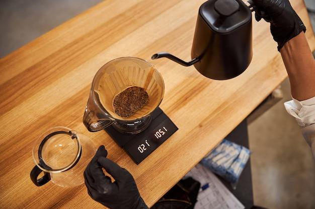 나무 테이블에 종이 필터를 통해 쏟아지는 뜨거운 커피