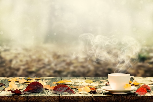 Hot coffee on the table on a autumn background