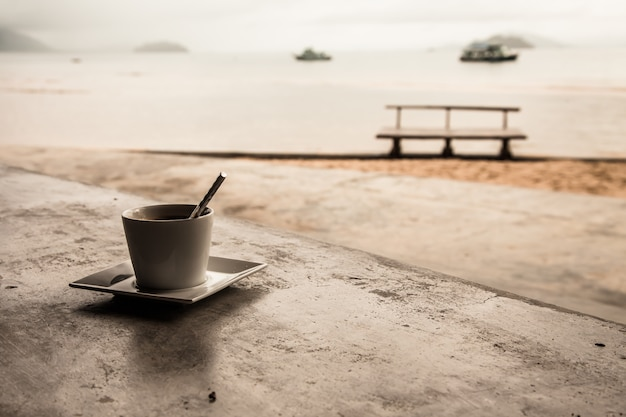 Hot coffee on tropical beach background