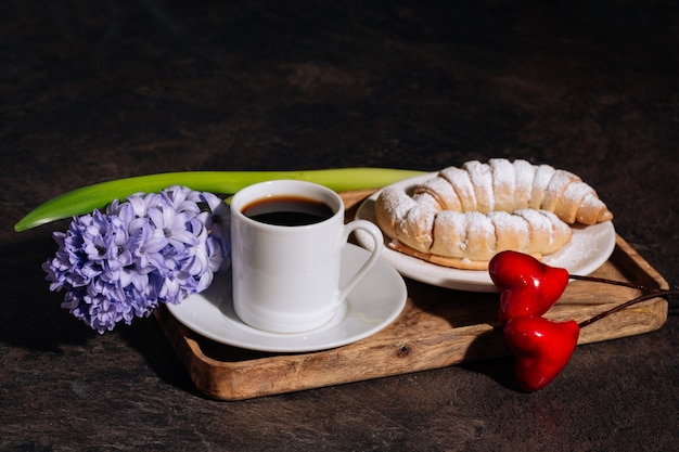 Hot coffee in white cup powdered croissant and flowers blue hyacinth on wooden tray