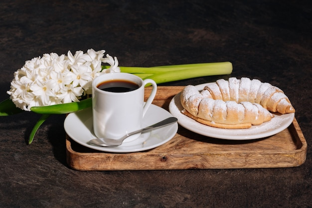 Hot coffee in white cup powdered croissant and flowers white hyacinth on wooden tray