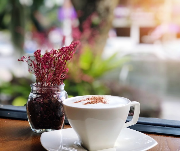 Hot coffee in a white cup on wooden table and flowers vase in coffee shop blur background