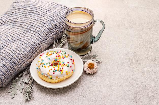 ドーナツとホットコーヒー。セーター、葉、花で気分を良くする冬の飲み物。