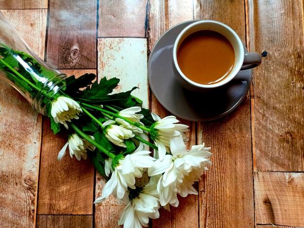 나무 배경에 흰 꽃을 넣은 뜨거운 커피