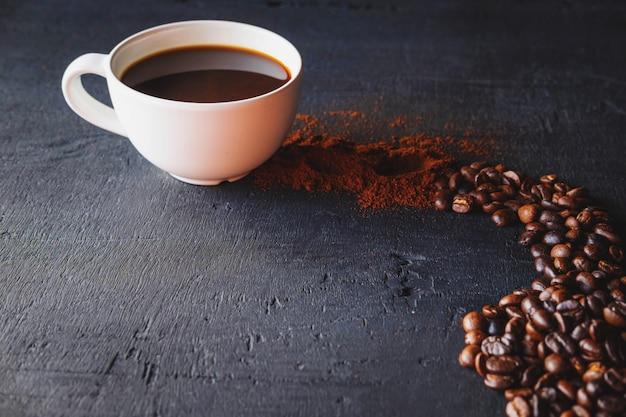 コーヒーパウダーと黒の背景にコーヒー豆とホットコーヒー