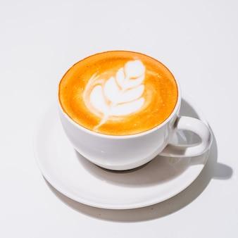 흰색 바탕에 라떼 아트와 흰색 머그를 넣은 뜨거운 커피