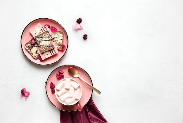 Hot coffee with marshmallows and chocolate on pink plates on gray surface