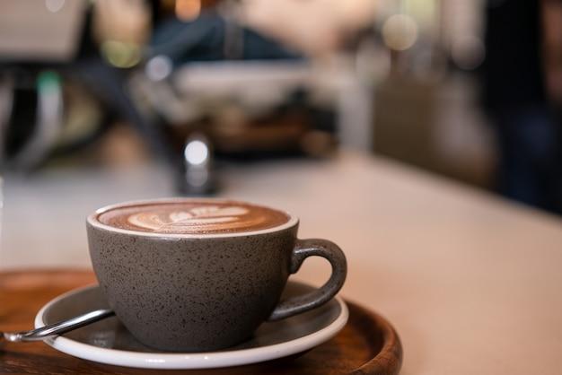 Горячий кофе с молочной пеной на деревянном столе в кафе