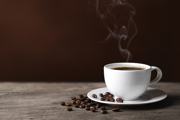 Hot coffee with roasted coffee beans on wood.