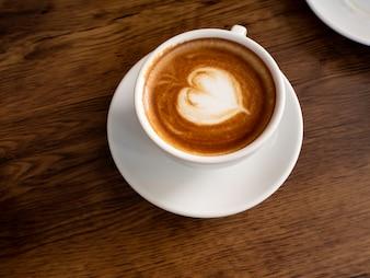 古い木製の板に柔らかい泡が付いている熱いコーヒー。