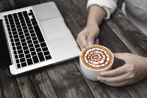 Hot coffee on wood table with laptop
