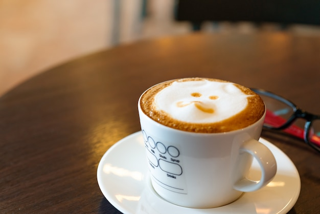 Hot coffee on wooden table with eye glasses