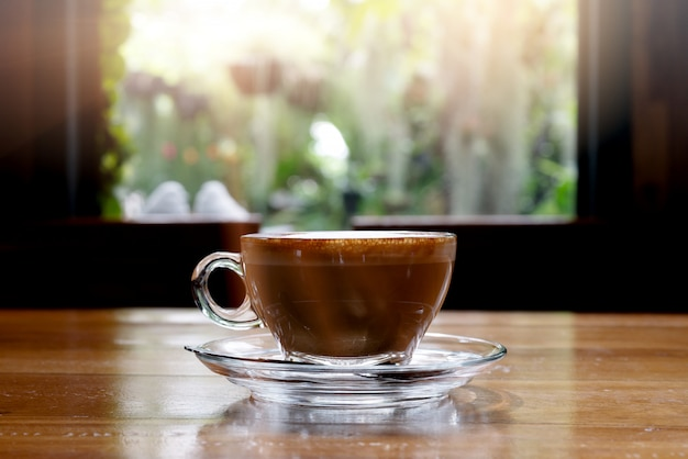 Hot coffee on wooden table with morning nice view on window