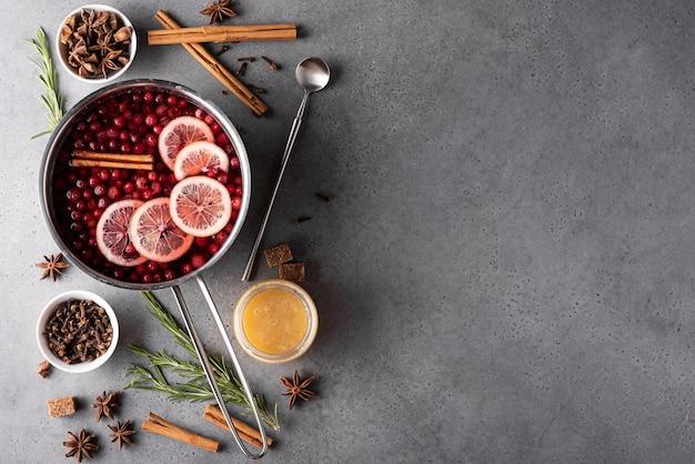 Горячий клюквенный напиток с лимонным медом и специями в серой кастрюле, вид сверху