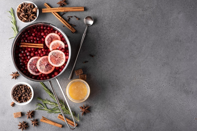 Hot cranberry drink with lemon honey and spices in a gray saucepan, top view