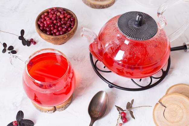 ガラスのカップに入った熱いクランベリーティーと明るい表面のティーポット。ベリーで温め、癒しのお茶。居心地の良い夜のための新年の飲み物。