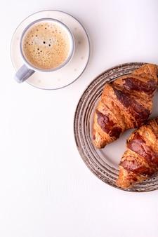 ホットクロワッサンと白い木製のテーブルの上のコーヒーカップ。朝の静物。テキスト用のスペースを持つトップビュー。