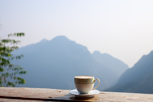Hot cup of coffee is placed on a wooden terrace and mountain background