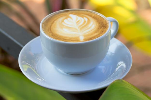 Hot cup of coffee latte art on steel