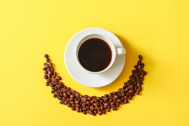 Hot cup of coffee with scattered beans on a yellow background