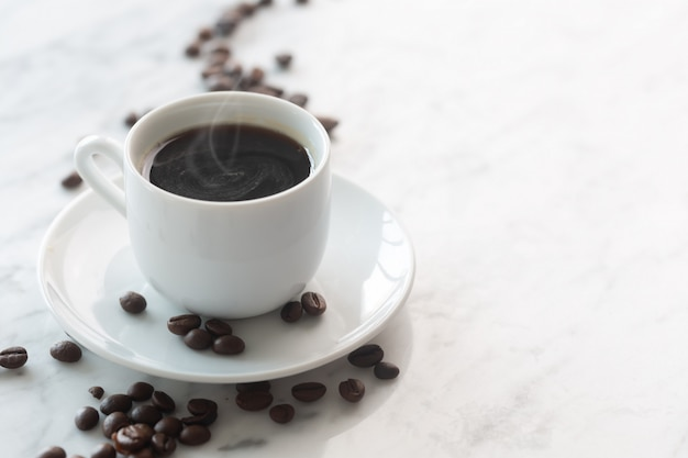 Hot cup of espresso or americano coffee in a traditional white cup on a table