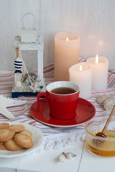 ストライプテーブルクロス、ろうそく、装飾的なハーブとガラスの花瓶に紅茶の熱いカップ