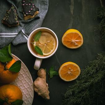 レモン、生姜、黒い表面のケーキ、上面図と緑茶のホットカップ