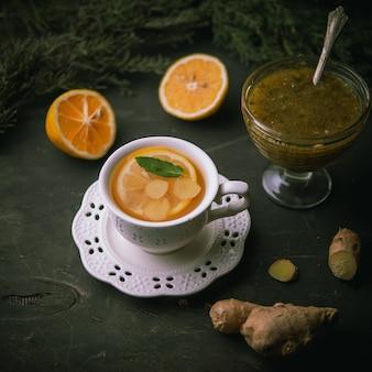 レモン、生姜、黒い表面のconfiture、上面図と緑茶の熱いカップ