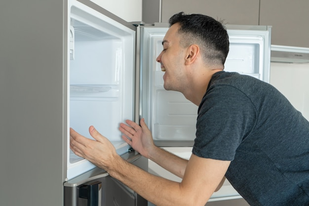On a hot day, the guy cools with his head in the refrigerator. broken air conditioner.