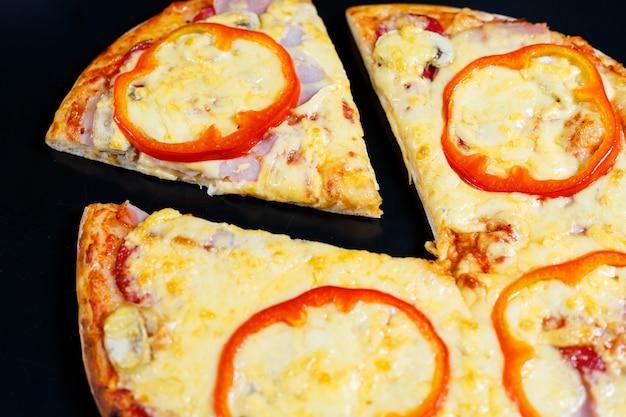 黒のテーブルの上に赤唐辛子と肉の厚い皮が付いたホットでおいしい自家製アメリカンピザ