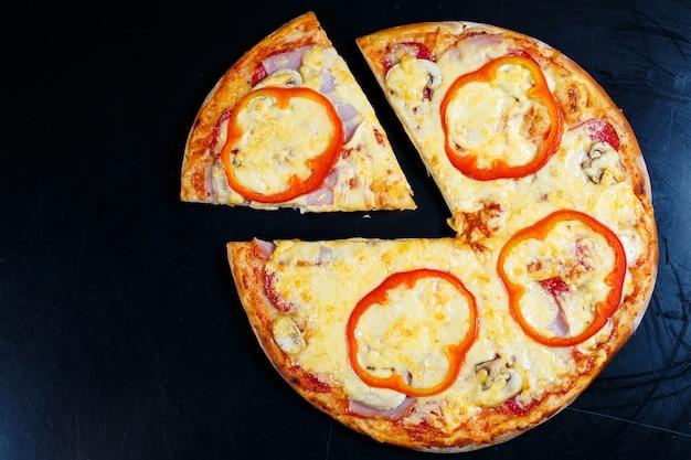 검은 테이블에 두꺼운 크러스트가 있는 붉은 고추와 고기를 곁들인 뜨거운 맛있는 홈메이드 아메리칸 피자