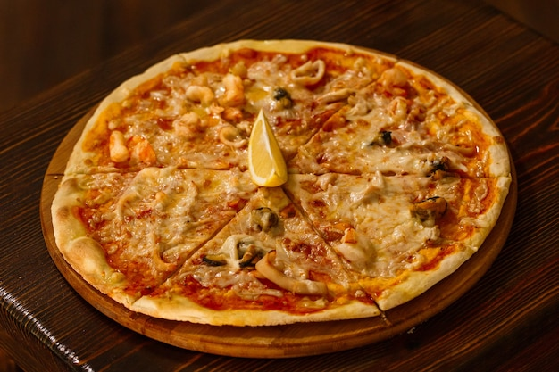Hot delicious pizza with melted cheese and seafood on a rustic wooden table.seafood pizza on a wood tray