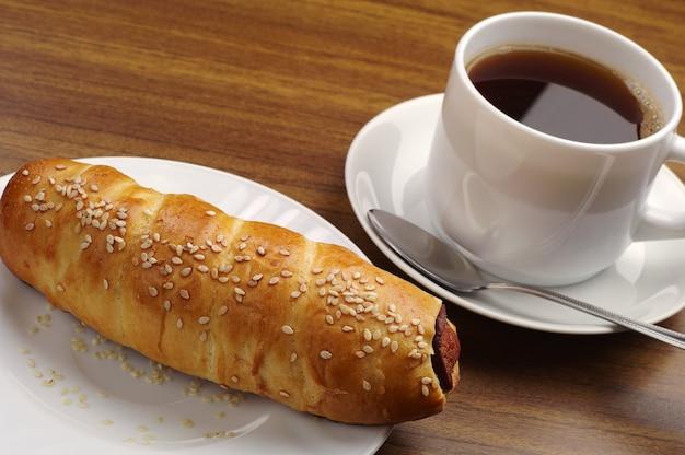 ホットドッグとテーブルの上のコーヒーのカップ