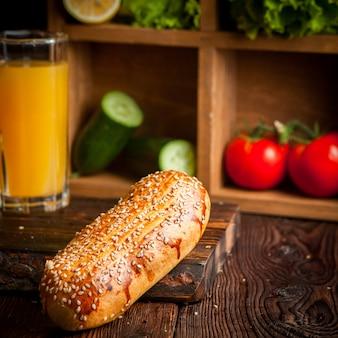 Булочка для хот-дога с апельсиновым соком и огурцами, помидорами и салатом на деревянной доске