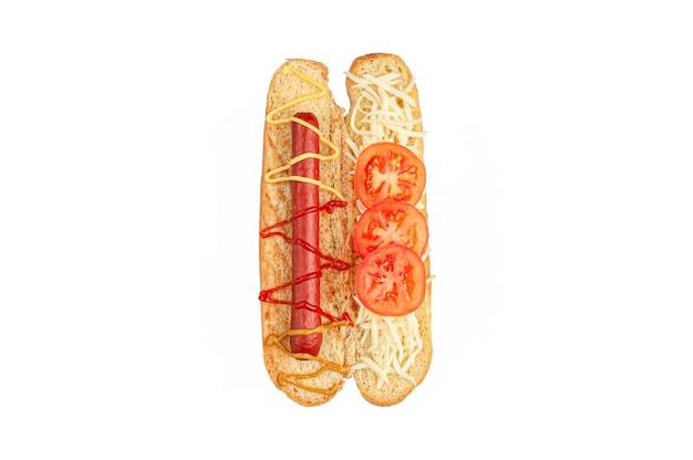 핫도그 재료. 자른 빵에는 소시지, 소스, 토마토, 모짜렐라 치즈 등의 재료가 들어 있습니다. 위에서 볼 수 있습니다. 흰색 배경. 외딴.