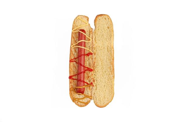 핫도그 재료. 자른 빵에는 소시지와 소스와 같은 재료가 들어 있습니다. 위에서 볼 수 있습니다. 흰색 배경. 외딴.