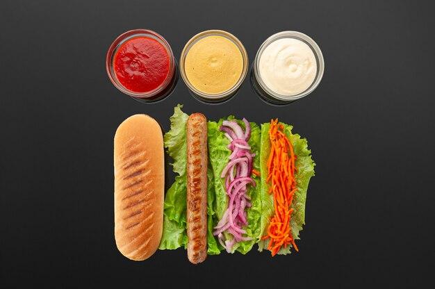Ингредиенты для хот-догов на темном столе
