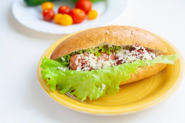 Хот-дог на тарелке с салатом