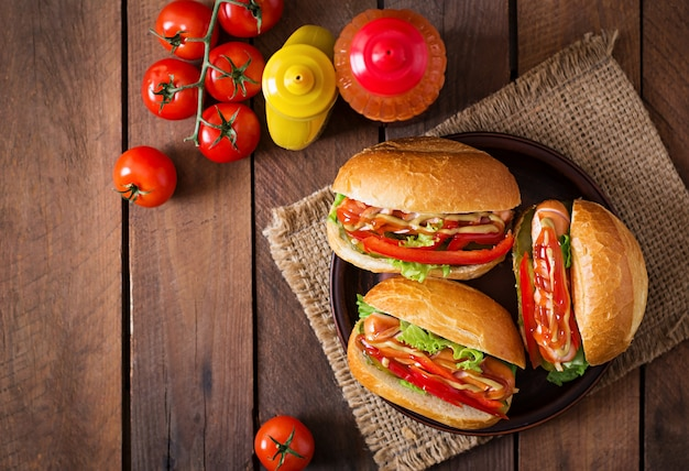 Hot dog - sandwich with pickles, paprika and lettuce on wooden background. top view