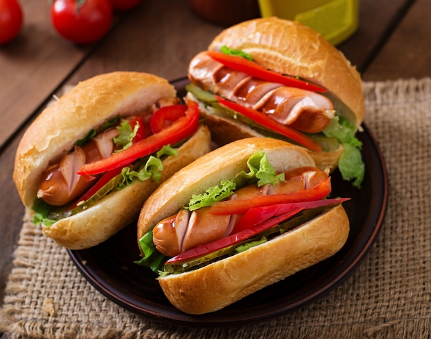 Hot dog - sandwich with pickles, paprika and lettuce on wooden background