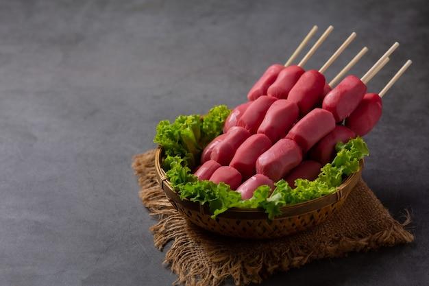 Hot dog o salsicce sulla superficie scura.