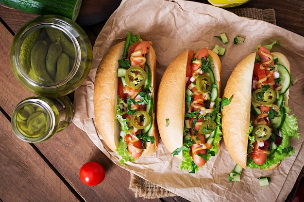 Hot dog with jalapeno peppers, tomato, cucumber and lettuce on wooden table