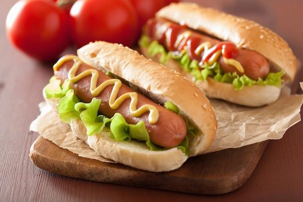 Хот-дог с кетчупом, горчицей и листьями салата