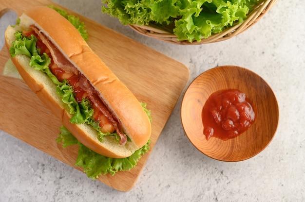 木製まな板の上のレタスとトマトソースのホットドッグ