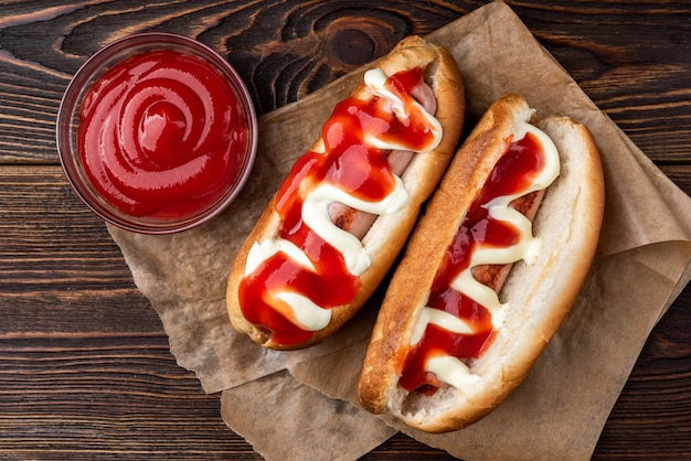 Hot dog with mayonnaise and ketchup on dark wooden background.