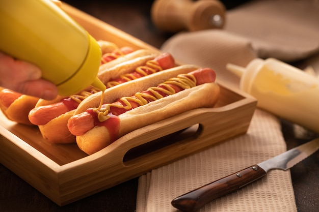 Hot dog with pepper, tomato, lettuce and salad mix on wooden.